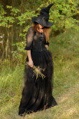 Woman in black dress and witch's hat, weeds in hands — Stock Photo
