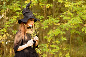Woman in witch's hat, smelling weeds in hands — Stock Photo