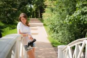 Smiling young woman leaning against a bridge railing — Stock Photo
