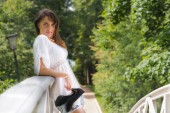 Young woman leaning against a bridge railing, stilettos in hand — Stock Photo