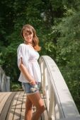 Smiling young woman standing on a plank bridge — Stock Photo