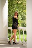 Woman in black dress standing back, leaning on a balustrade — Foto Stock