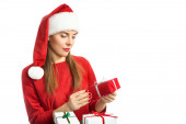 Young woman in red winter hat looking at gift box — Stock Photo