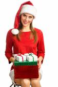 Woman in red santa hat holding present boxes — Stok fotoğraf