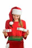 Woman in red santa hat holding present boxes — Stockfoto