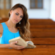 Young woman sitting on bench and reading book — Stock Photo #77036395