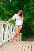 Young woman leaning on balustrade, looking down, hand in pocket — Stock Photo