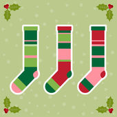 Winter holidays background with colorful baby socks for gifts from Santa Claus and  branch of Holly — 图库矢量图片
