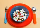 Different particolored pills on a plate — Stock Photo