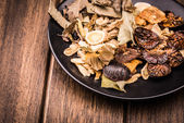 Chinese traditional herbs in the black plate. — Stock Photo