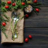 Table with cutlery, herbs, tomatoes and spices — Stock Photo