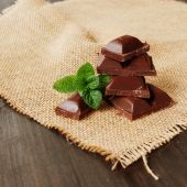 Pieces of chocolate with mint lying on a wooden — Stock Photo