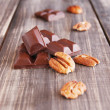Pieces of chocolate with walnuts lying on a wooden — Stock Photo #78309412