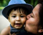 Smiling latino baby being kissed on cheek — Stock Photo