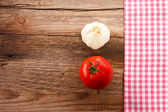 Wooden board with a checkered tablecloth, garlic and tomato — Stock Photo