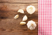 Wooden board with a checkered tablecloth and garlic — Stock Photo