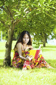 Woman lying on the green grass and reading — Stock Photo