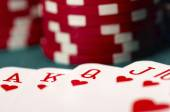 Cards showing a royal flush with some casino tokens — Stock Photo