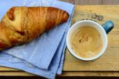 Blue coffe mug with fresh coffee and cream and croissant bread with a light grey blue tea towel with broidery on a old used wooden brakfast table in vintage style — Stock Photo