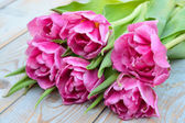 Close up of Bunch of pink purple tulips on used old grey blue knotted wood — Stock Photo