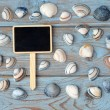 Empty black chalk board on a old knotted used wooden background with sea beach shells for a beach style mood board layout — Stock Photo #71592705
