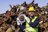 Trabajador en junkyard mantener rotor como trofeo brillante — Foto de Stock