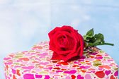 Heart-shaped Valentines Day gift box with red rose over a Backg — Stock Photo