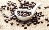 Coffee in spoon and sack background — Stock Photo