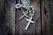 Necklace white crucifix on old wooden table — Stok fotoğraf
