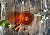 Star anise in tea glass vibrant on wooden and cinnamon background — Stock Photo