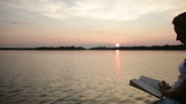 Vrouw leest bij zonsondergang — Stockvideo