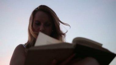 女性の日没で読書 — ストックビデオ