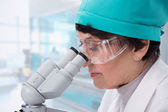 Biologist looking through a microscope — Stock Photo