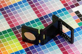 Close-up of a loupe on a colorful test print — Stock Photo
