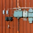 Electric junction boxes, retro style on red wall — Stock Photo #69944033