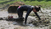 Woman crawling on her knees through the mud — Stock Photo
