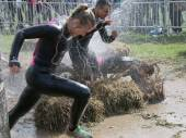 Woman and man running, one woman has fallen in the mud — Stock Photo