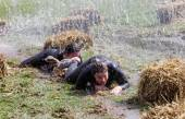 Two woman crawling in the mud between sheaf of hay — Stock Photo