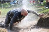 Man fighting to get through the mud, squirted with water, electr — Stock Photo