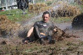 Man falling in the mud squirted with water — Stock Photo