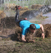 Man in blue tshirt makes a spectacular overturn in the mud — Stock Photo