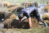 Muscular built man crawling over sheaf of hay — Stock Photo