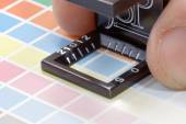 Close-up of a loupe and hand on a colorful test print — Stock Photo