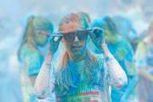 Young woman covered with blue color powder fixing the glasses — Stok fotoğraf