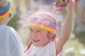Happy kid squirting pink color powder over the head — Stock Photo