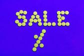 Verkoop teken gekleed met gele snoepjes — Stockfoto