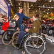 Motopark-2015 (BikePark-2015). Young couple visitors in wheelchairs looking exhibition stand with motorcycles and ATVs. — Stock Photo #66808387