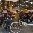 Motopark-2015 (BikePark-2015). Young couple visitors in wheelchairs looking exhibition stand with motorcycles and ATVs. — Stock Photo #66808419