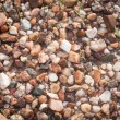 Small rocks cover a floor with some dirt and grass, Background a — Stock Photo #74140175
