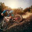 Man riding a mountain bike in downhill style at sunrise. Extreme sports on a bicycle. — Stock Photo #52217905
